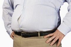 穿紧的正式衬衣的一个肥胖人的中央部位  库存图片