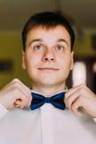 穿戴他的蝶形领结的激动的年轻英俊的新郎 免版税库存图片