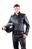 穿黑皮夹克和裤子的英俊的骑自行车的人人拿着摩托车盔甲 免版税库存照片
