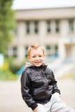 穿黑皮夹克的可爱的小男孩画象  库存照片