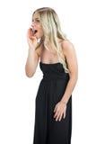 穿黑礼服的可爱的金发碧眼的女人尖叫 免版税库存图片