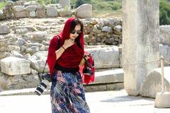 穿戴红色围巾的旅游妇女走与两台照相机 免版税图库摄影