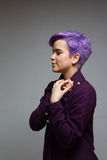 穿紫罗兰色外套的紫罗兰色短头发的妇女,举行递a 库存照片