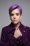 穿紫罗兰色外套的紫罗兰色短头发的妇女,举行递a 图库摄影