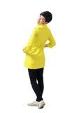 穿黄色外套的年轻嬉戏的妇女背面图转动和微笑对照相机 库存图片