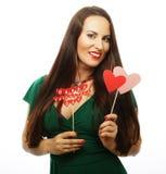 穿绿色礼服的美丽的妇女拿着纸心脏 库存图片