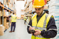 穿黄色背心的被聚焦的工作者使用手扶 免版税库存照片