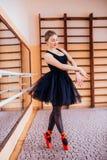穿黑芭蕾舞短裙的芭蕾舞女演员做锻炼在训练大厅里 库存照片