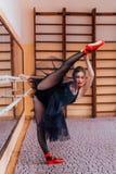 穿黑芭蕾舞短裙的芭蕾舞女演员在训练大厅里做分裂 免版税图库摄影