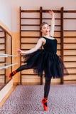 穿黑芭蕾舞短裙的年轻微笑的芭蕾舞女演员做锻炼在训练大厅里 库存图片