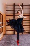 穿黑芭蕾舞短裙的年轻微笑的芭蕾舞女演员做锻炼在训练大厅里 图库摄影