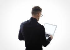 穿黑衬衣和握当代笔记本手的年轻有胡子的商人照片  白色空的屏幕准备好您m 库存照片