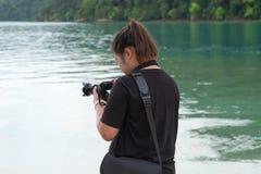 穿黑衬衣的亚洲妇女站立在海滩和使用camer 免版税库存图片