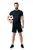 穿黑运动服的微笑的足球或futsal球员拿着球在他的看照相机的胳膊下 库存照片