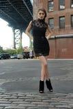 穿黑minidress的妇女站立在曼哈顿桥梁下 库存图片