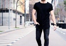 穿黑T恤杉和牛仔裤的特写镜头观点的年轻肌肉人走在现代城市的街道上 蠢材 免版税图库摄影