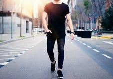穿黑T恤杉和牛仔裤的年轻肌肉人走在现代城市的街道上 被弄脏的背景 库存照片