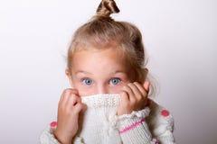 穿knited毛线衣的儿童女孩掩藏她的面孔在衣领神色 免版税库存图片