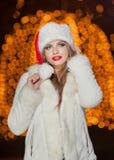 穿Xmas帽子和白色皮大衣的时兴的夫人室外。年轻美丽的妇女画象冬天样式的。明亮的图片 免版税库存照片