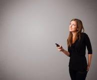 突出和拿着有复制空间的小姐一个电话 免版税库存图片