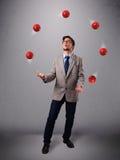 突出和玩杂耍与红色球的年轻人 库存图片
