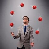 突出和玩杂耍与红色球的年轻人 免版税库存照片