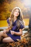 突出在一个公园的美丽的端庄的妇女在秋天 免版税图库摄影