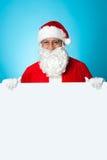 突出在一个空白广告董事会之后的变老的圣诞老人 库存图片