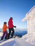 突出在一间冷淡的客舱旁边的二个女性滑雪者 库存照片