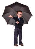 突出在伞下的黑色衣裳的男孩 免版税库存图片