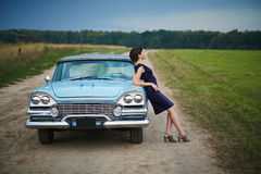 突出在减速火箭的汽车附近的美丽的夫人 免版税图库摄影