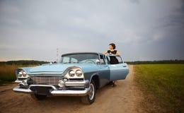 突出在减速火箭的汽车附近的美丽的夫人 免版税库存照片