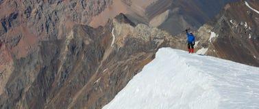 突出在山上面的登山家 免版税库存照片