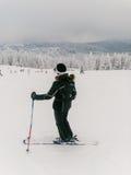 突出在山坡的女性滑雪者 库存图片