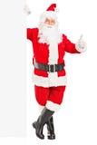 突出在广告牌旁边的愉快的圣诞老人 免版税库存图片