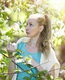 突出在开花的苹果树附近的新可爱的妇女 库存图片