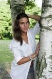 突出在桦树附近的逗人喜爱的女孩 图库摄影