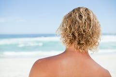 突出在海滩的一个白肤金发的人的背面图 免版税库存照片