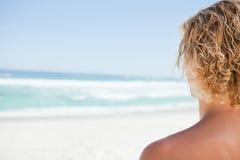 突出在海滩的一个白肤金发的人的背面图 免版税库存图片