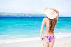 突出在海滩的美丽的少妇享用星期日 免版税库存照片