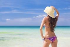 突出在海滩的美丽的少妇享用星期日 库存照片