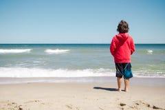 突出在海滩的男孩 库存图片