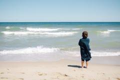 突出在海滩的男孩 库存照片