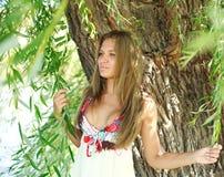 突出在结构树下的美丽的女孩 免版税图库摄影