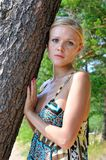 突出在结构树的美丽的白肤金发的妇女 图库摄影