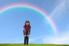 突出在绿草的微笑的亚裔小女孩在雨之下 免版税库存图片
