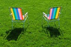 突出在草的二把五颜六色的椅子 免版税库存照片