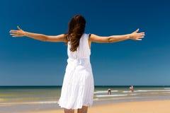 突出在阳光下在海滩的可爱的妇女 库存照片