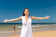 突出在阳光下在海滩的可爱的妇女 库存图片