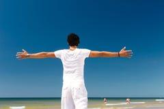 突出在阳光下在海滩的英俊的人 图库摄影